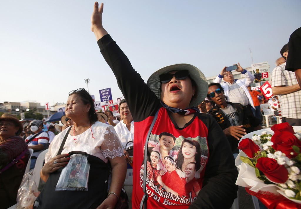 A supporter of Pheu Thai Party wearing a t-shirt of former Prime Ministers Thaksin Shinawatra and Yingluck Shinawatra raise her hand during an electio...