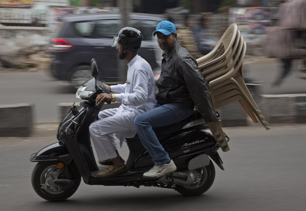 In this Dec. 17, 2018, photo, two men transport chairs purchased from a shop at the Nampally furniture market in Hyderabad, India. Such furniture mark...