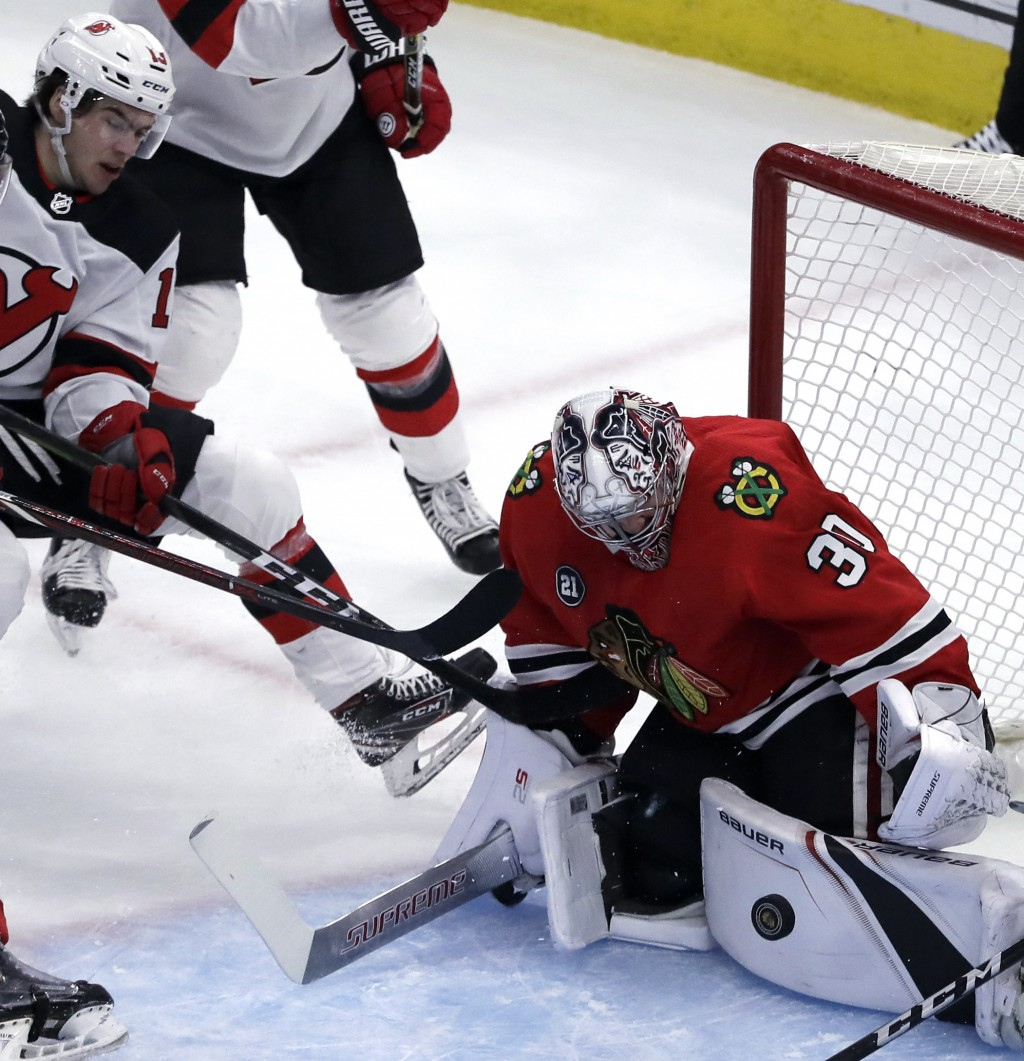 Chicago Blackhawks goalie Cam Ward, right, blocks a shot by New Jersey Devils center Nico Hischier during the first period of an NHL hockey game Thurs...