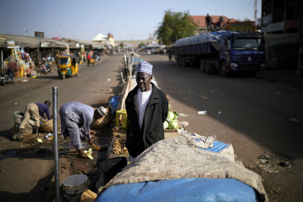 A Nigerian salesman stands in the middle of the normally busy street outside the central market in Kaduna, Nigeria, Saturday Feb. 16, 2019. Nigeria's ...