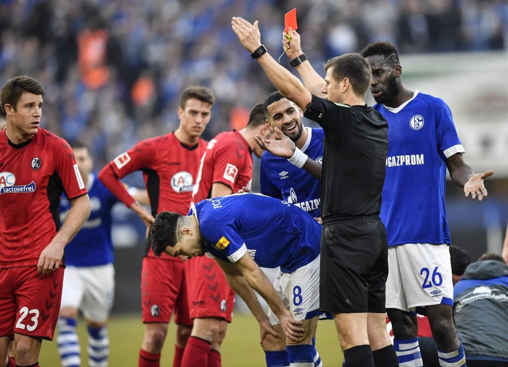 Referee Frank Willenborg, center, shows the red card to Schalke's Suat Serdar, left, during the German Bundesliga soccer match between FC Schalke 04 a...