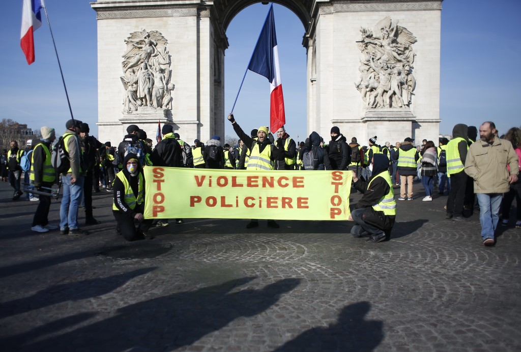 """Yellow vest protesters gather at the Arc de Triomphe with a banner reading """"Stop police violence"""", Saturday, Feb.16, 2019 in Paris. Yellow vests prote..."""