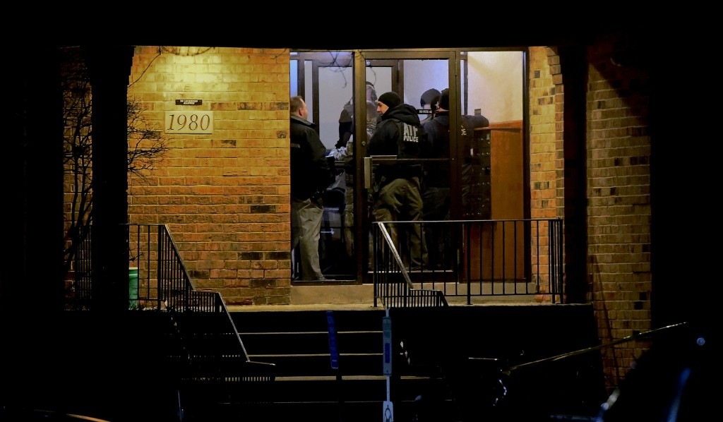 Investigators enter an apartment building Friday, Feb. 15, 2019, in Aurora, Ill., where a man who police say fatally shot several people and injured p...