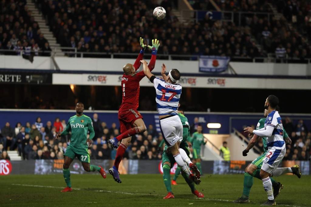 Watford's goalkeeper Heurelho Gomes, second left, collects the ball past Queens Park Rangers' Matt Smith during the English FA Cup 5th round soccer ma...