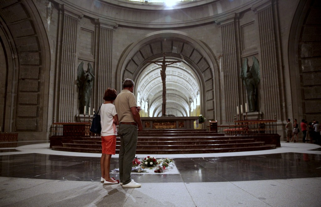 FILE  - In this file photo taken on Friday, July 13, 2018, people look at the tomb of former Spanish dictator Francisco Franco inside the basilica at ...