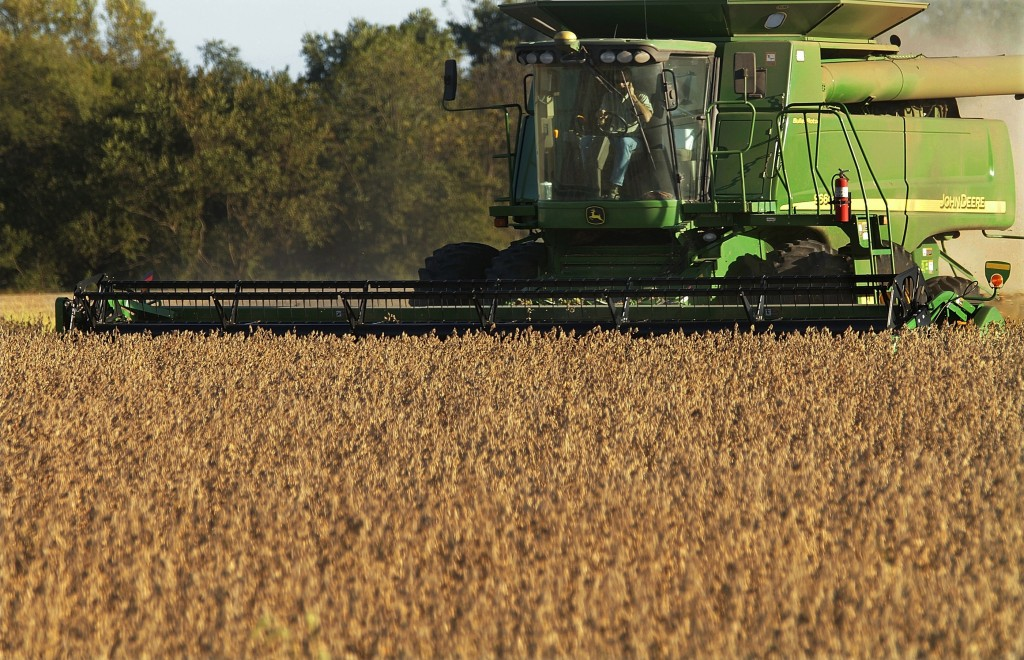 FILE - In this Sept. 30, 2010 file photo, central Illinois farmers harvest soybeans in Pleasant Plains, Ill.  Deere, a manufacturer that faces threats...