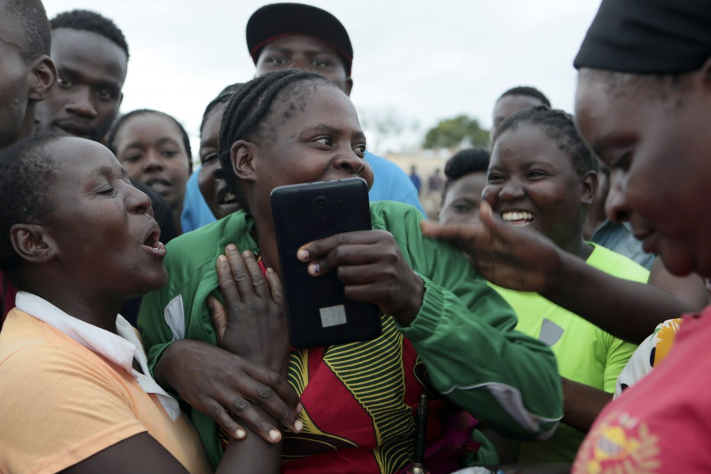 Families react after hearing eight artisanal miners survived after rains flooded mines on the outskirts of Kadoma, west of Harare, Zimbabwe, Saturday,...