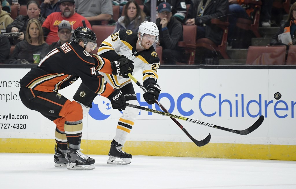 Boston Bruins center Joakim Nordstrom, right, passes the puck while under pressure from Anaheim Ducks defenseman Cam Fowler during the first period of...