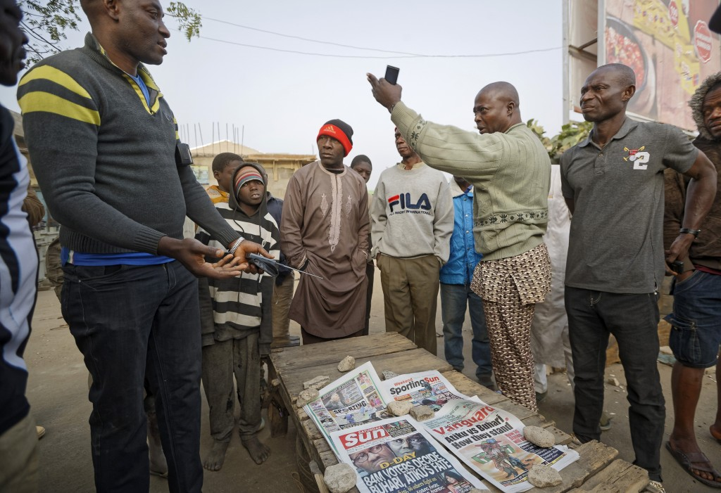 Nigerians discuss the overnight developments at a newspaper stand selling copies of papers that printed before the postponement was announced, in the ...