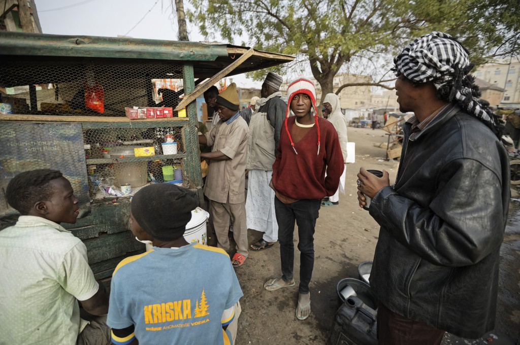 Newspaper distributors take hot drinks from a roadside stall in the morning next to a newspaper stand in Kano, in northern Nigeria Saturday, Feb. 16, ...