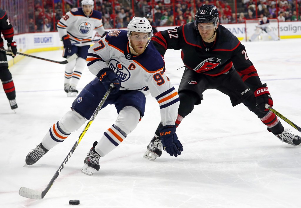 Edmonton Oilers' Connor McDavid (97) drives the puck around Carolina Hurricanes' Brett Pesce (22) during the first period of an NHL hockey game Friday...