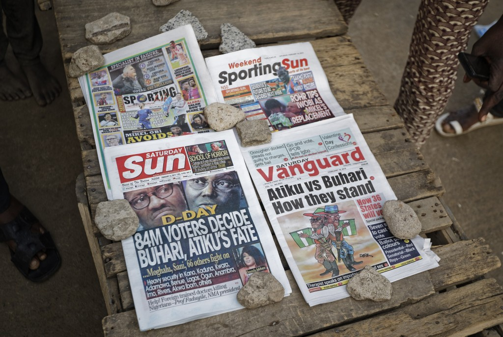 Newspapers that printed before the postponement was announced, sit on a stand in the morning in Kano, northern Nigeria Saturday, Feb. 16, 2019. Nigeri...
