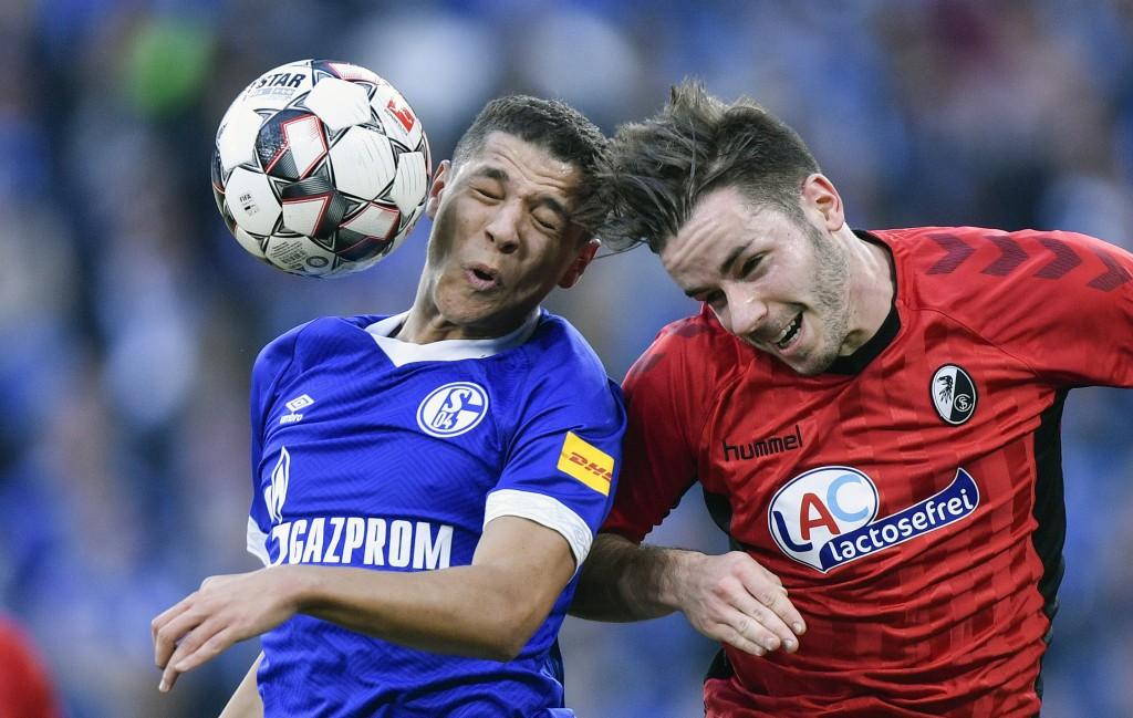Schalke's Amine Harit, left, and Freiburg's Christian Guenter challenge for the ball during the German Bundesliga soccer match between FC Schalke 04 a...