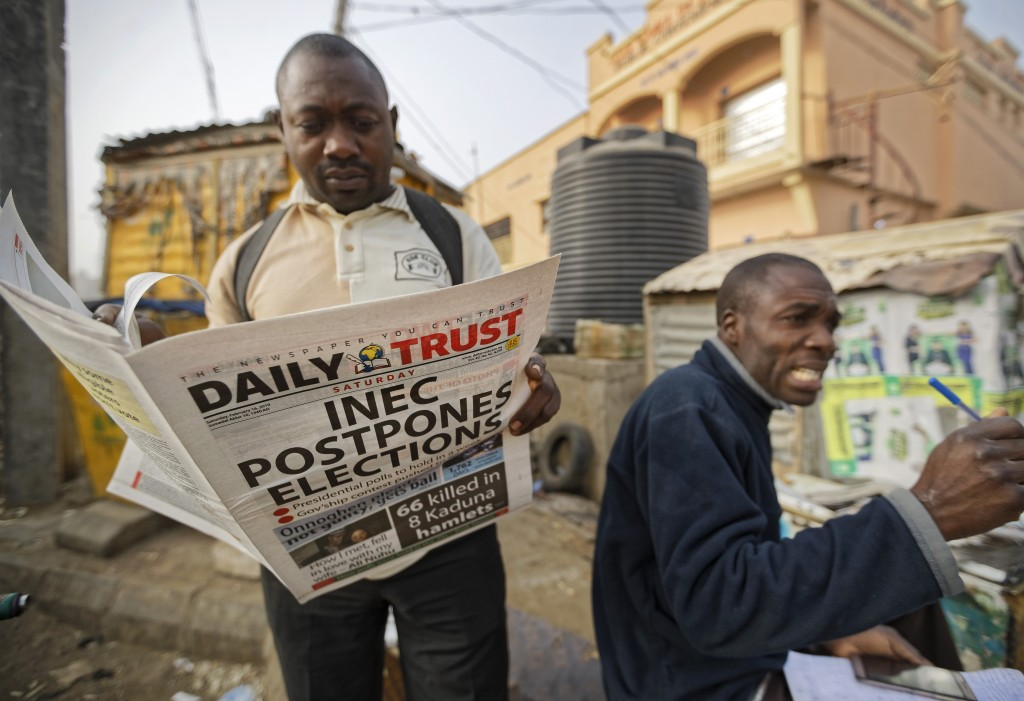 A man reads a copy of a newspaper which managed to print the news of the postponement in time, in the morning at a newspaper stand in Kano, in norther...