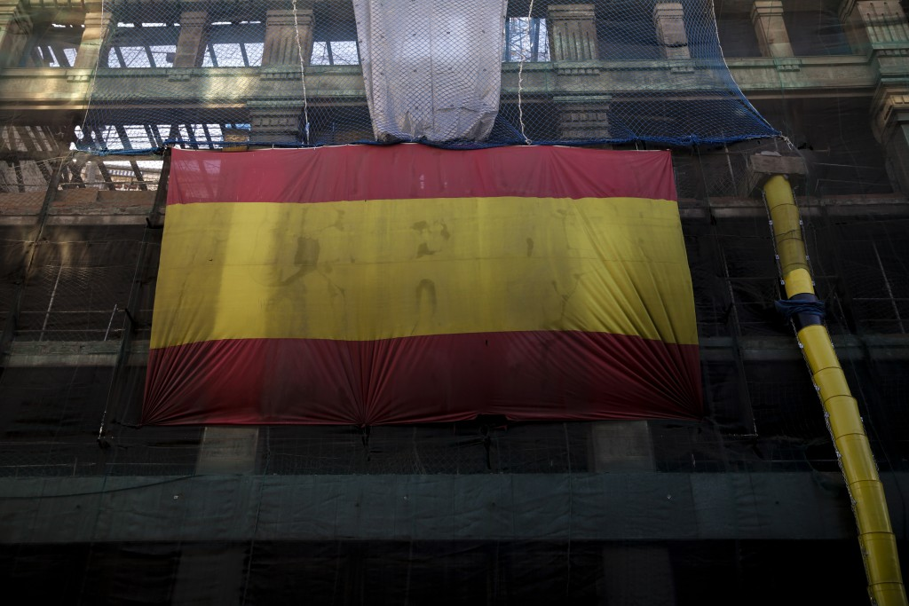A huge Spanish flag hangs from a building under construction in downtown Madrid, Spain, Friday, Feb. 15, 2019. The prime minister of Spain has called ...