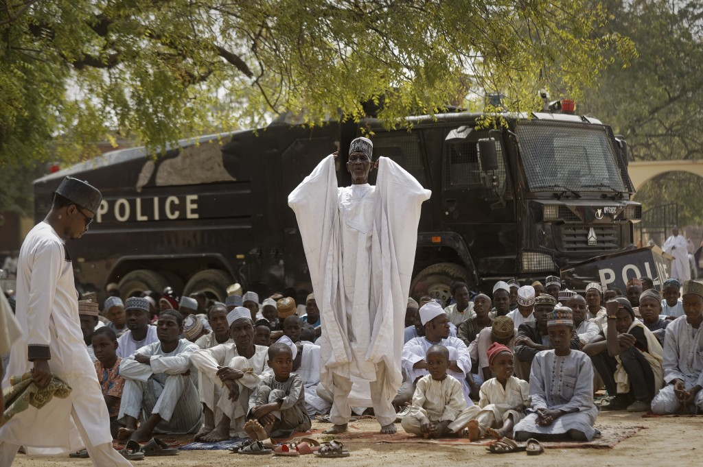 Muslims make traditional Friday prayers in front of a police riot truck, providing security due to the ongoing general threat of attacks by Islamic ex