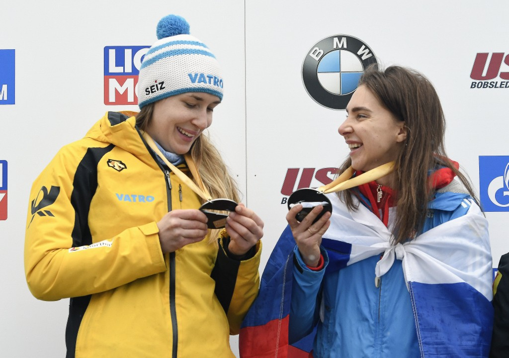 Gold medalists Jacqueline Loelling, left, of Germany, and Elena Nikitina, of Russia, compare their medals after tying for first place in the women's s...