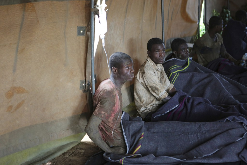 Survivors of artisanal miners sit in a tent after rains flooded mines on the outskirts of Kadoma, west of Harare, Zimbabwe, Saturday, Feb, 16, 2019. A...