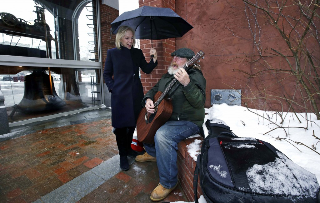 Sen. Kirsten Gillibrand, D-NY, sings along with street musician Kevin Clark, who plays a Cat Stevens' song, while touring Main Street in Concord, N.H....