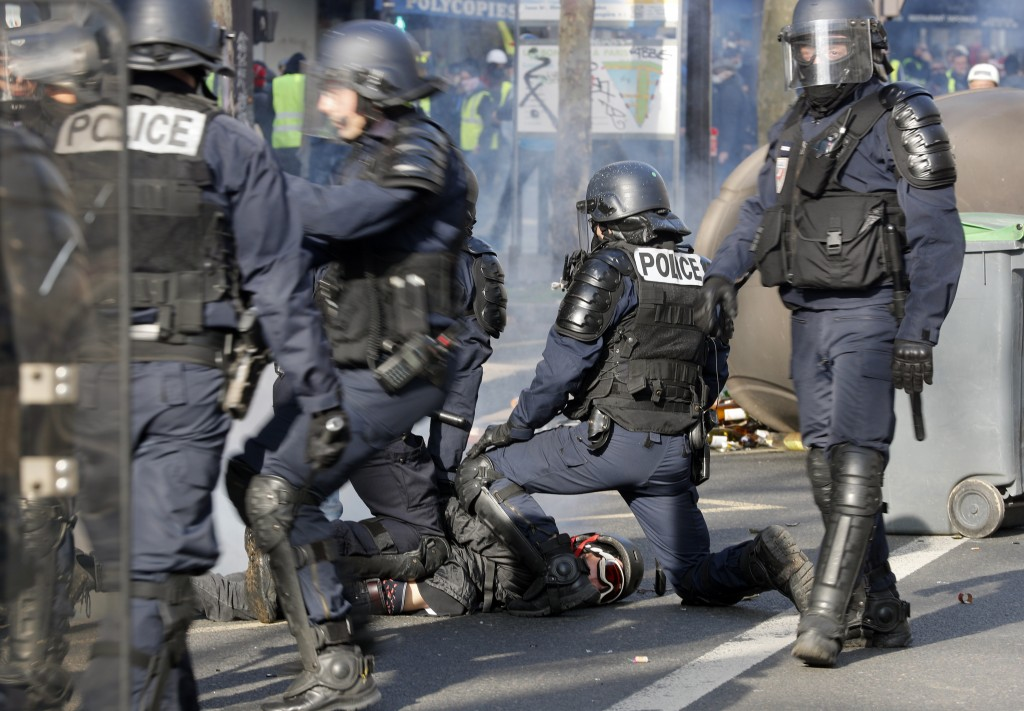 Riot police officers detain a protester during a demonstration Saturday, Feb.16, 2019 in Paris. Yellow vest protesters are holding scattered demonstra...