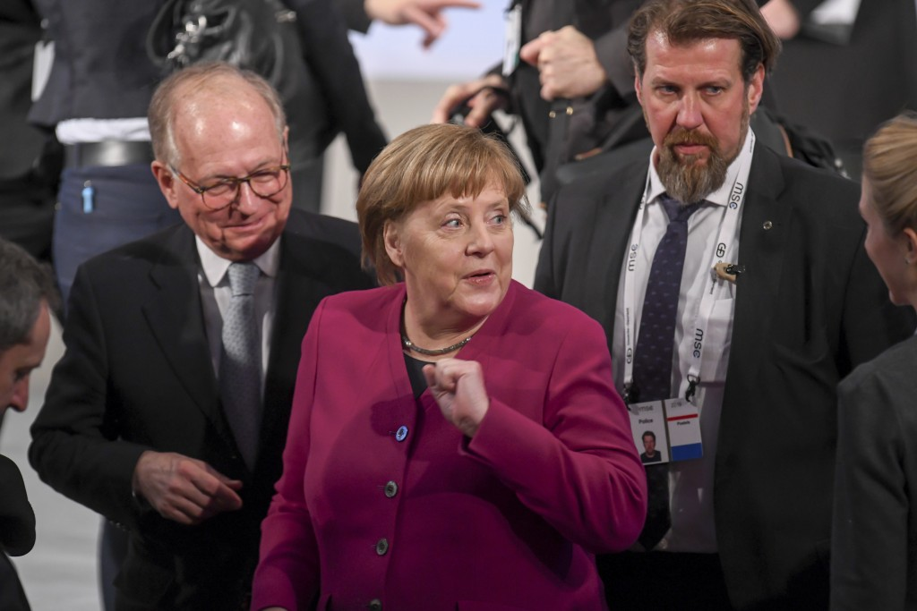 German Chancellor Angele Merkel, center, arrives for a meeting during the Munich Security Conference in Munich, Germany, Saturday, Feb. 16, 2019. (Tob...