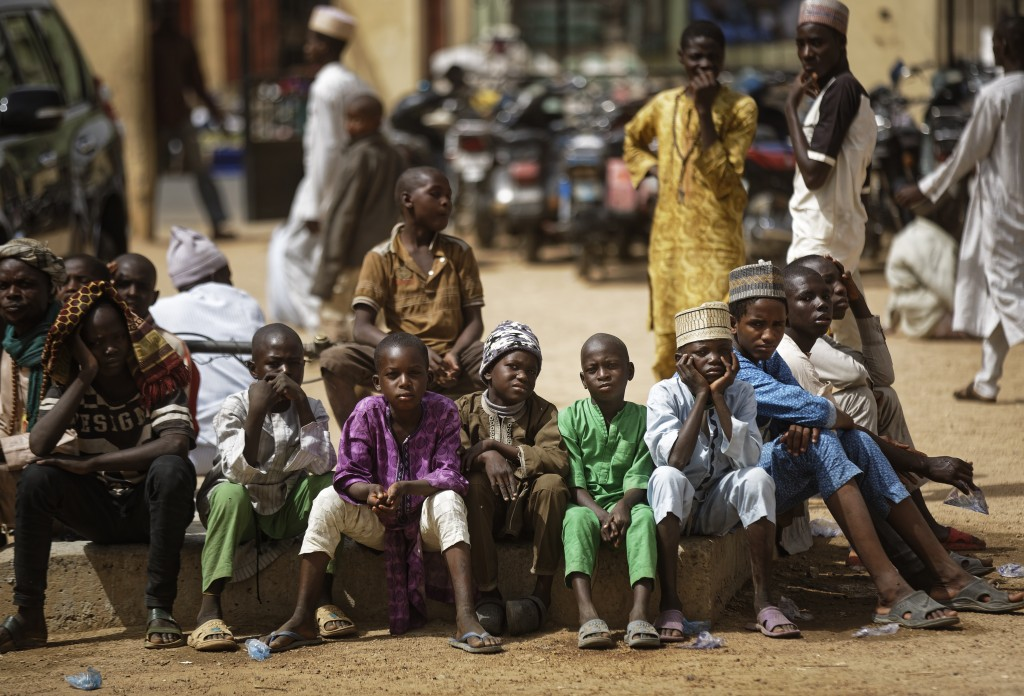 Young Muslim boys wait for traditional Friday prayers to begin at a mosque near to the Emir's palace a day prior to the start of the elections, in Kan