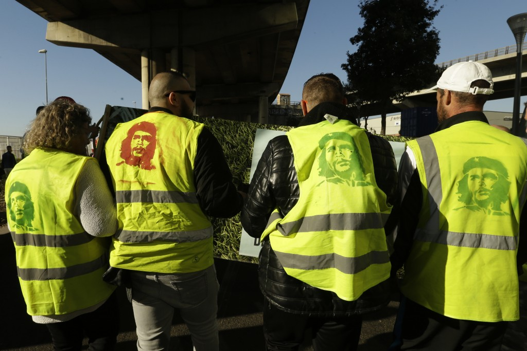 Yellow vest protesters with portraits of Che Guevara on their vest march during a demonstration Saturday, Feb.16, 2019 in Marseille, southern France. ...