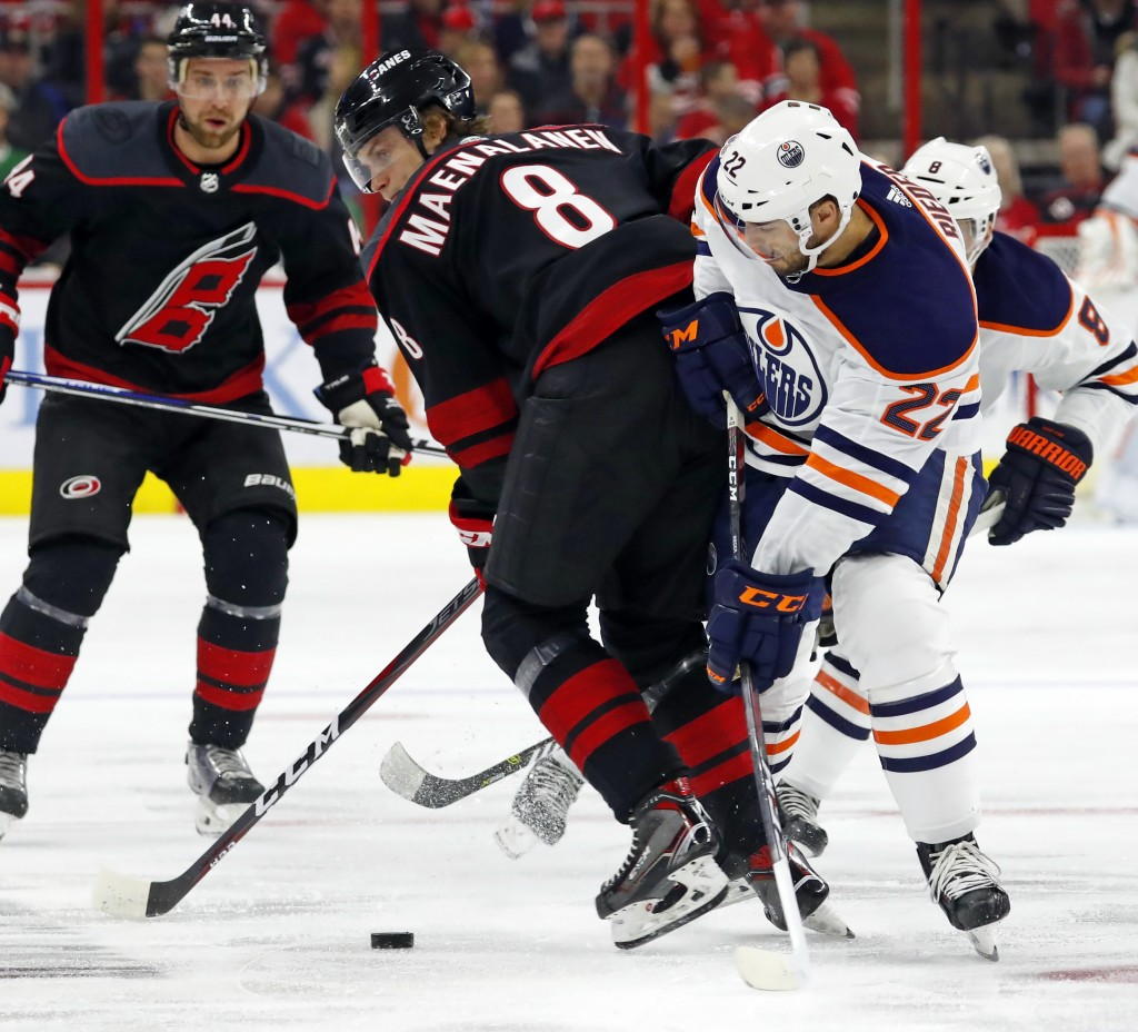 Carolina Hurricanes' Saku Maenalanen (8) and Edmonton Oilers' Tobias Rieder (22) compete for the puck during the first period of an NHL hockey game Fr...