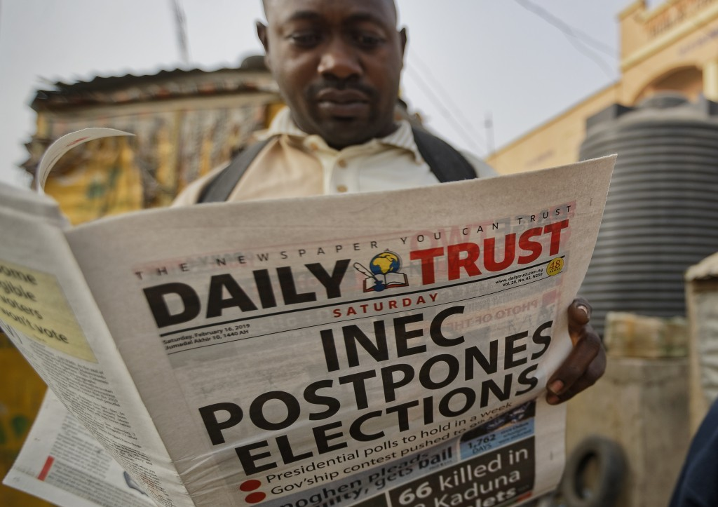 A man reads a copy of a newspaper which managed to print the news of the postponement in time, in the morning at a newspaper stand in Kano, northern N...
