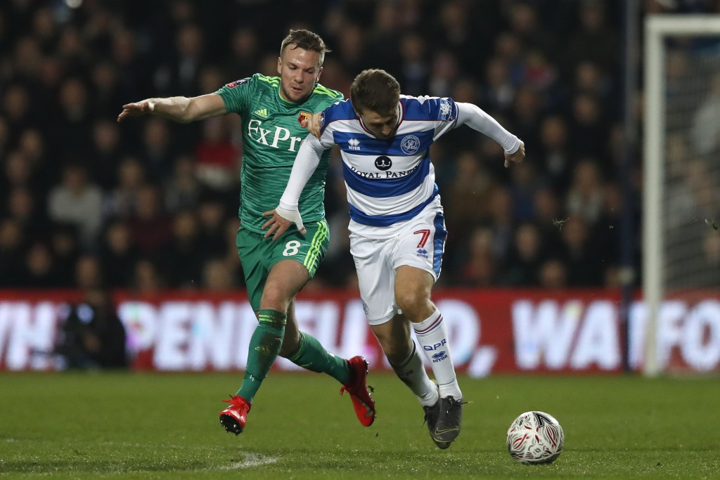 Queens Park Rangers' Luke Freeman, right, runs with the ball past Watford's Tom Cleverley during the English FA Cup 5th round soccer match between Que...