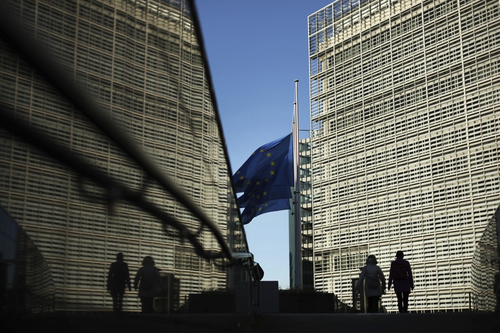 Passers-by walk next to the European Commission headquarters in Brussels, Friday, Feb. 15, 2019. British Prime Minister Theresa May suffered an embarr...