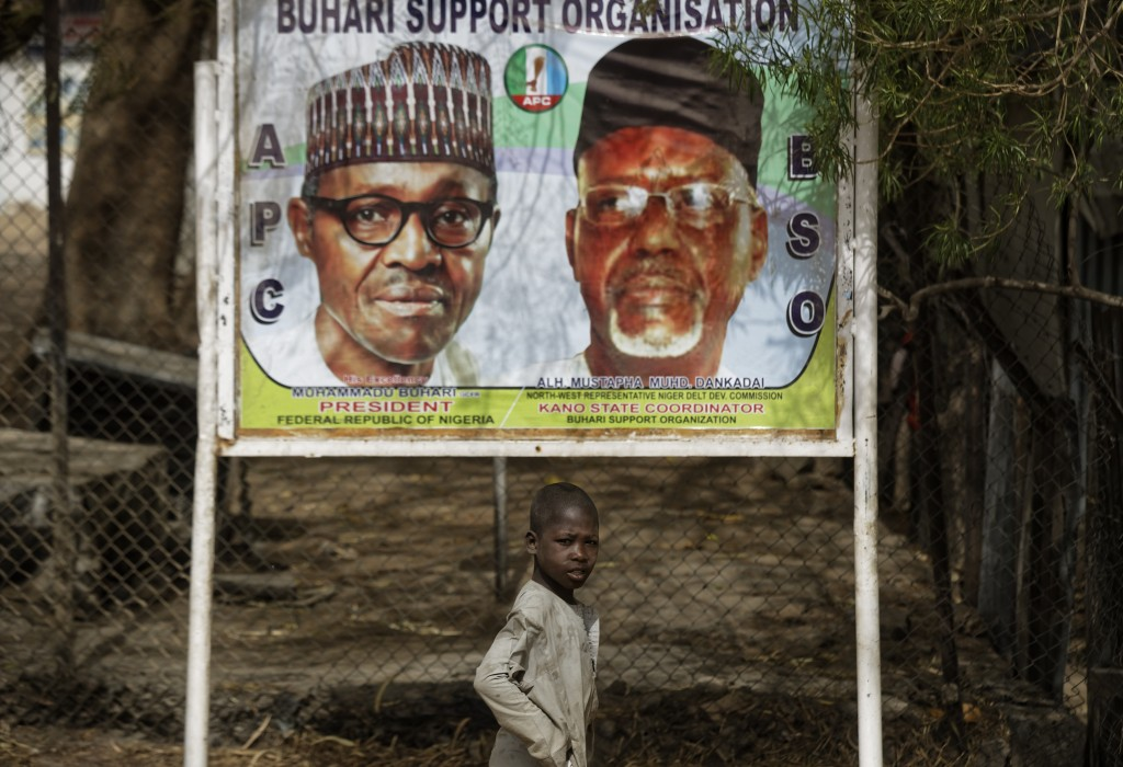 A young boy scavenges for re-sellable items from garbage on the streets, as he walks past a sign showing incumbent President Muhammadu Buhari, left, a...