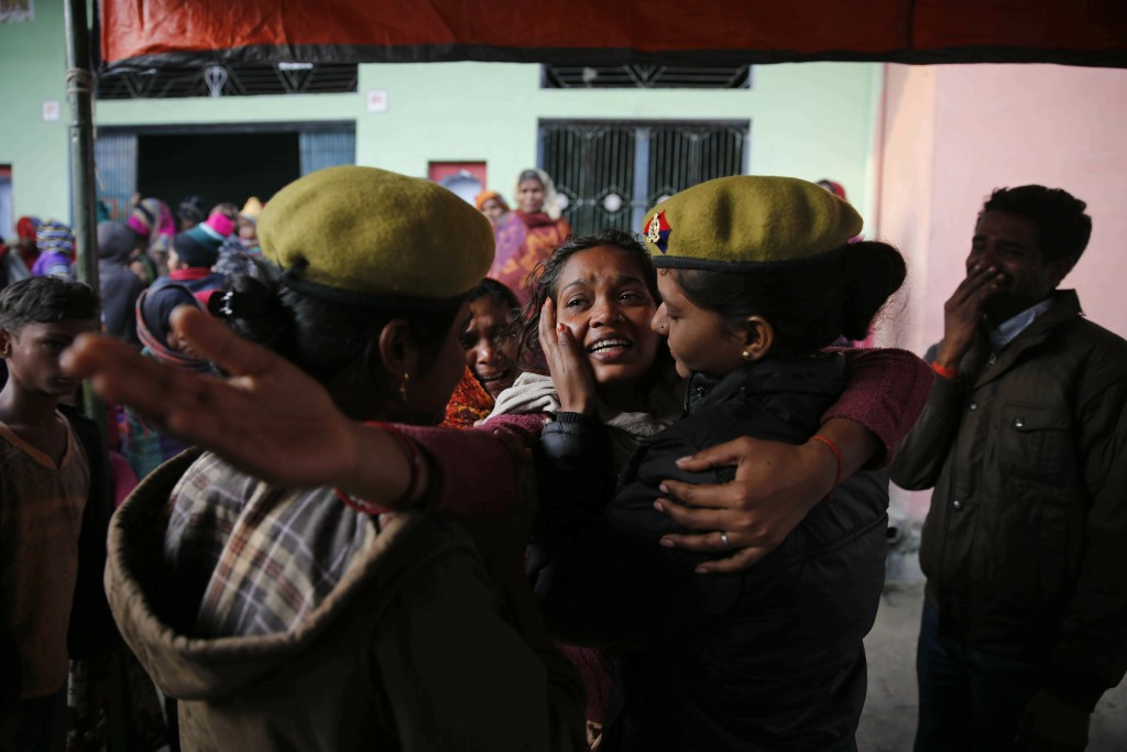 A policewoman comforts a relative of paramilitary soldier Mahesh Yadav, who was killed in Thursday's explosion in Kashmir, mourn at their home in Tudi...