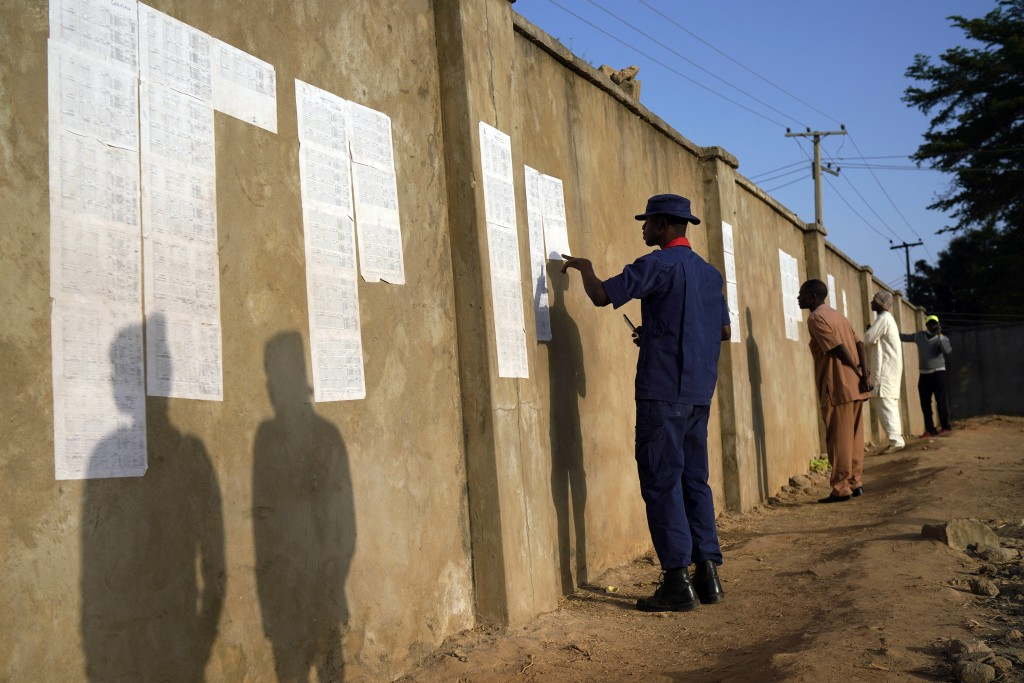 Nigerians check voters' lists at a polling station in Kaduna, Nigeria, Saturday, Feb. 16, 2019. Nigeria's electoral commission delayed the presidentia...