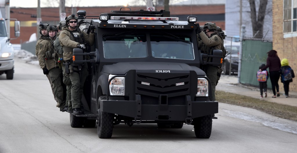 Police officers ride on a vehicle Friday, Feb. 15, 2019, near the site of a shooting at a manufacturing plant in Aurora, Ill., that police said left s