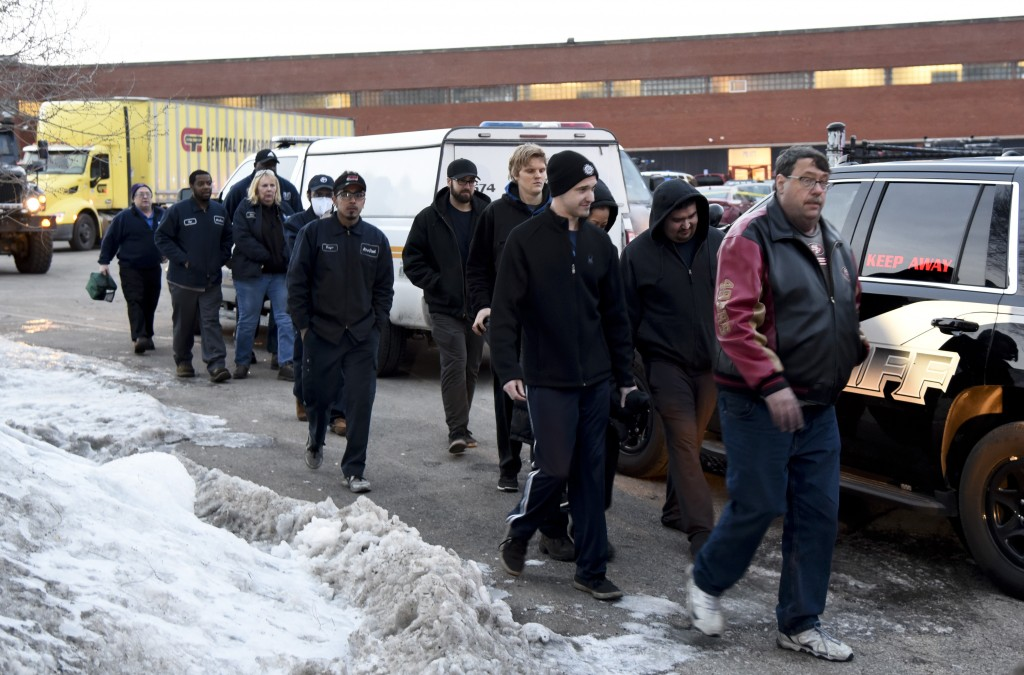 Employees are escorted from the scene of a shooting at a manufacturing plant Friday, Feb. 15, 2019, in Aurora, Ill., that police said left several peo...
