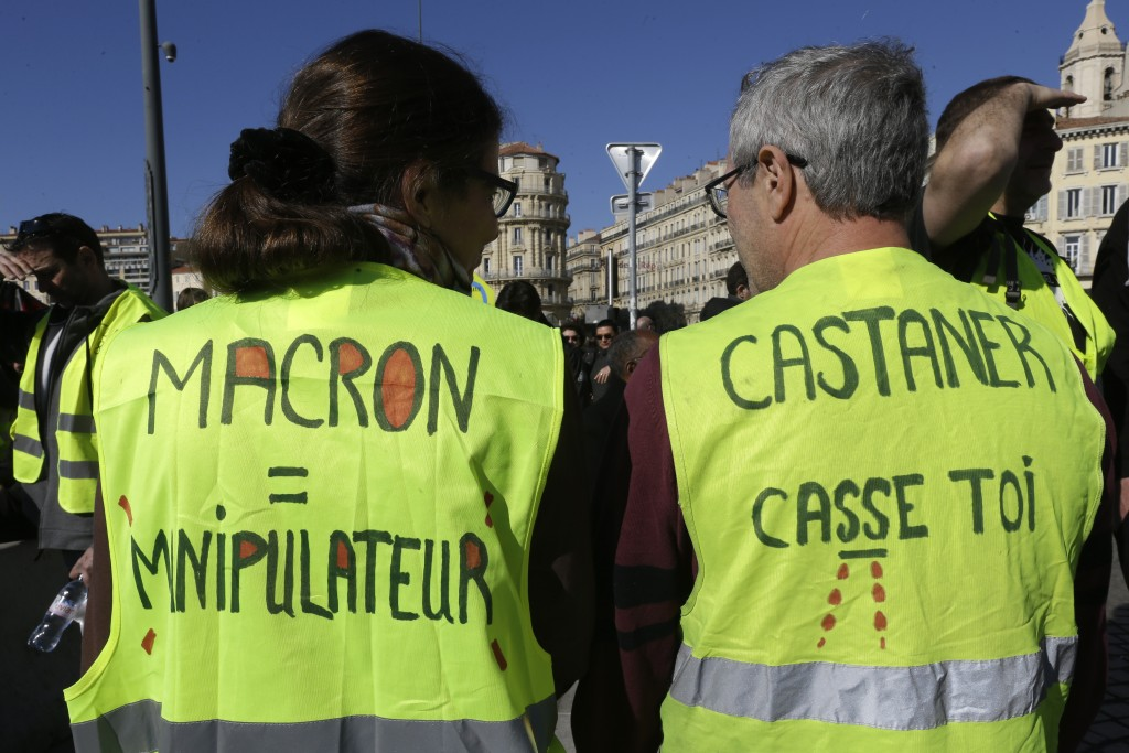 """Yellow vest protesters wear jackets reading """"Macron manipulative"""" and """"Castaner go away"""" referring to French Interior Minister Christophe Castaner, du..."""