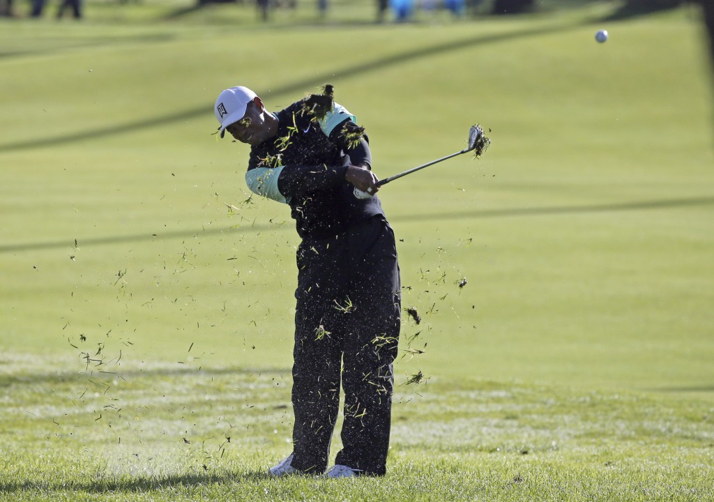 Tiger Woods hits from the second fairway rough as first-round play continues in the Genesis Open golf tournament at Riviera Country Club in the Pacifi...