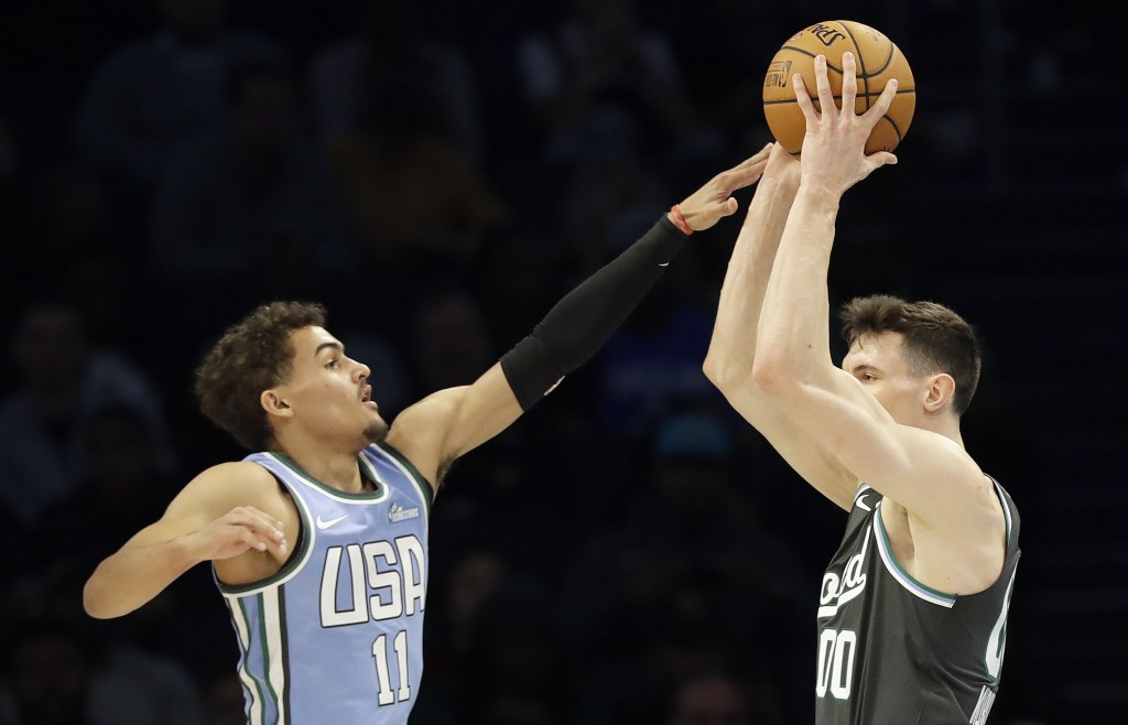 U.S. Team's Trae Young, of the Atlanta Hawks works against World Team's, Rodions Kurucs, of the Brooklyn Nets during the NBA All-Star Rising Stars bas...