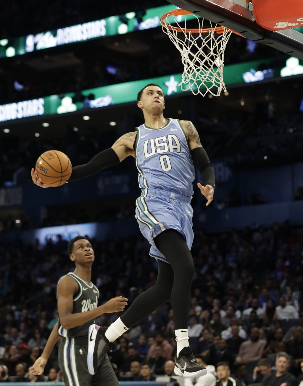 U.S. Team's Kyle Kuzma, of the Los Angeles Lakers heads to the hoop for a dunk against the World Team during the NBA All-Star Rising Stars basketball ...