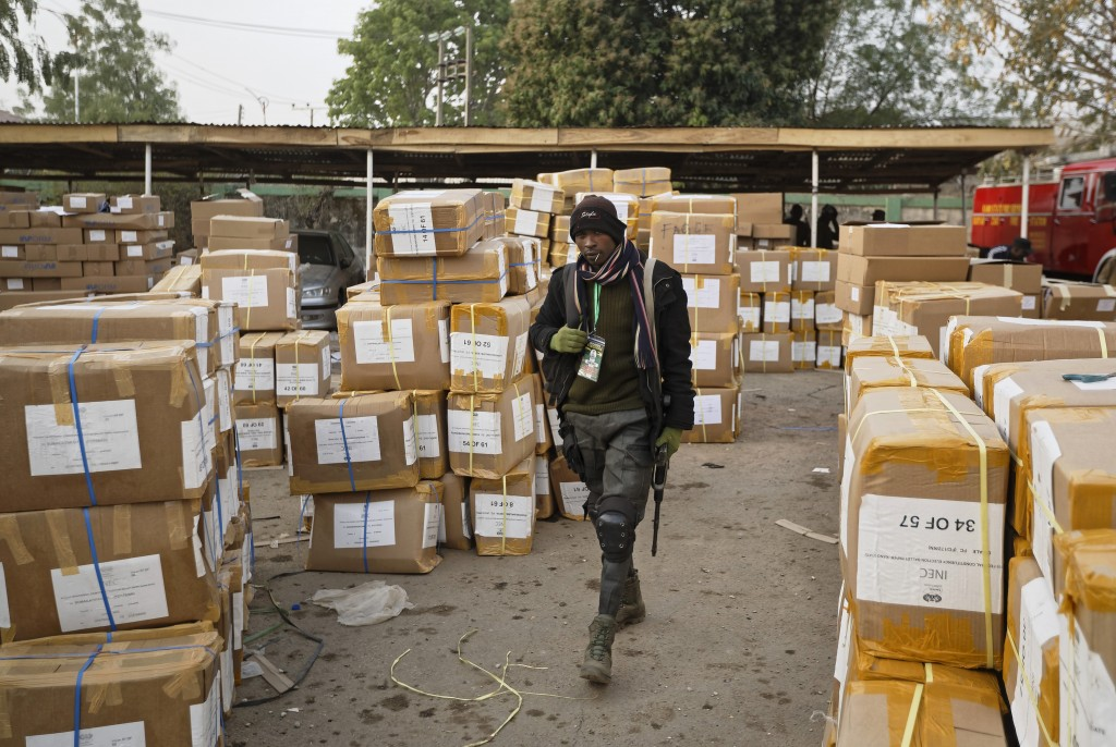 A police officer keeps guard over electoral materials still stacked in boxes at the offices of the Independent National Electoral Commission in Kano, ...