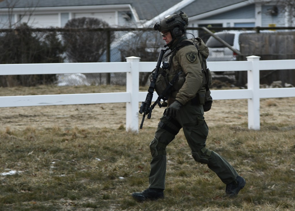 A law enforcement officer works at the scene of a shooting at the Henry Pratt Co. on Friday, Feb. 15, 2019, in Aurora, Ill. Officials say several peop...