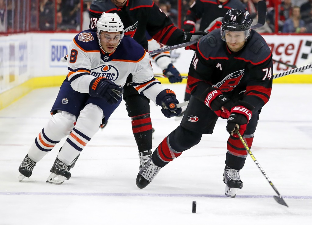 Carolina Hurricanes' Jaccob Slavin (74) and Ty Rattie (8) vie for the puck during the first period of an NHL hockey game, Friday, Feb. 15, 2019, in Ra...