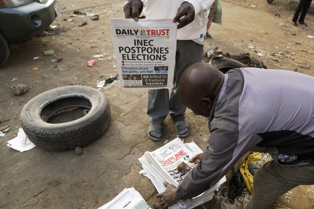 Newspaper sellers bring copies of a newspaper which managed to print the news of the postponement in time, in the morning at a newspaper stand in Kano...