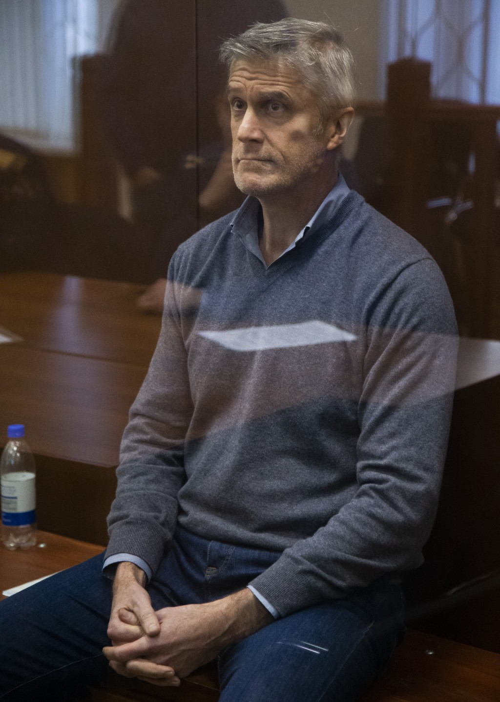 Founder of the Baring Vostok investment fund Michael Calvey looks through a cage's class in the court room in Moscow, Russia, Saturday, Feb. 16, 2019....