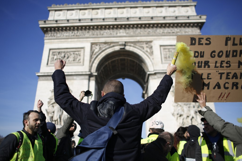 Yellow vest protesters gather at the Arc de Triomphe, Saturday, Feb.16, 2019 in Paris. Yellow vests protesters keep pressure on French President Emman...
