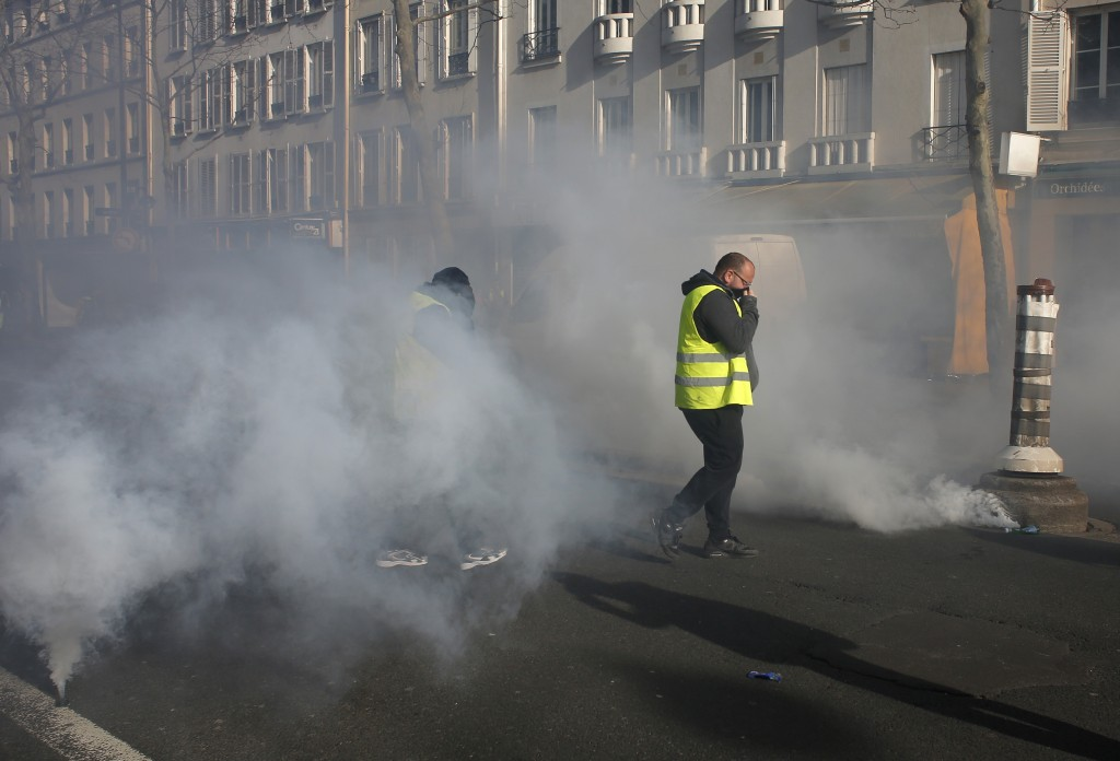Yellow vest protesters walk through tear gas during a demonstration Saturday, Feb.16, 2019 in Paris. Yellow vest protesters are holding scattered demo...