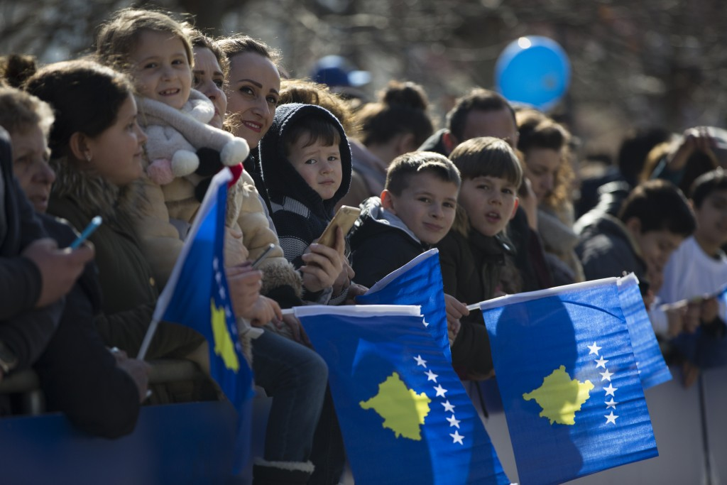 Kosovars wave national flags as they wait to watch a military parade, during celebrations to mark the 11th anniversary of independence in Pristina, Su...