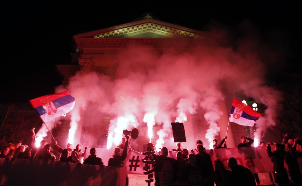 People light flares in front of the Serbian parliament building during a protest march against populist President Aleksandar Vucic in Belgrade, Serbia...
