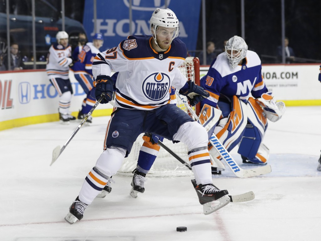 New York Islanders goaltender Robin Lehner (40) watches as Edmonton Oilers' Connor McDavid (97) looks to control the puck during the first period of a...